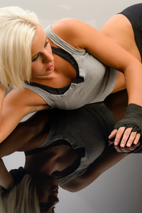 Female kick-boxer laying down on black plexiglass fitness studio
