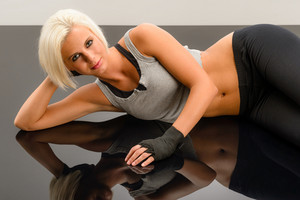 Female kickboxer laying down on black plexiglass at fitness studio
