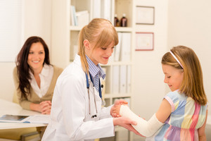 Female pediatrician checking bandage of girl broken arm