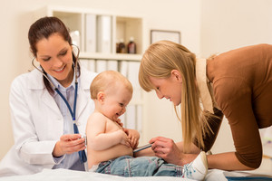 Female pediatrician checking cute baby girl with stethoscope mother assistance