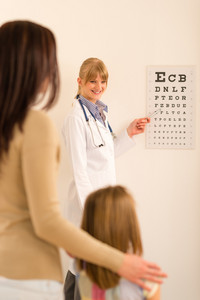 Female pediatrician ophthalmologist child pointing at eye chart medical office