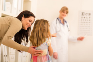 Female pediatrician pointing at eye chart mother and child visit