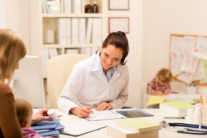 Female pediatrician smiling mother baby patient sitting at office desk