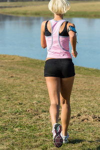 Female runner jogging by water park sunny day fit body