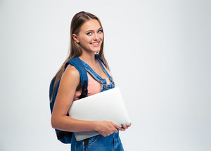 Female student holding laptop and looking at camera