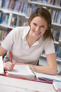 Female student sat at desk smiling to camera