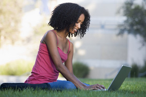 Female student using laptop outside