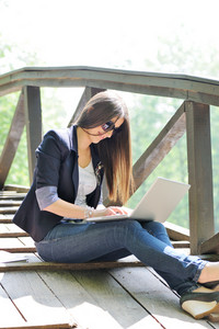 Female studing using laptop while sitting on a wooden bridge in nature