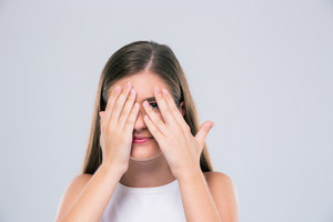 Female teenager covering her eyes