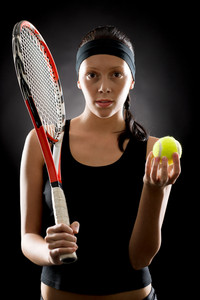 Female tennis player with racket and balll on black background