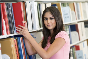Female university student selecting book from shelf