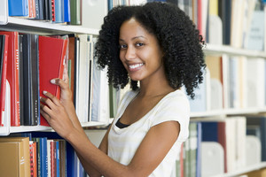 Female university student selecting library book from shelf