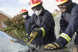 Firefighters breaking a car windscreen to help a car crash victim