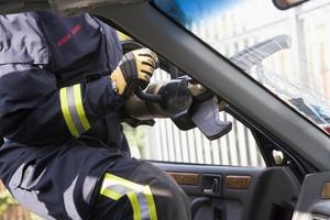 Firefighters breaking a car windscreen to help a car crash victim
