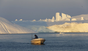 Fisherman on a small boat traveling past a sunlit iceberg