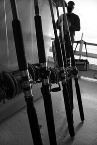 Fishing rods and bait caster reels lined up in a row on a deep sea fishing boat in black and white.