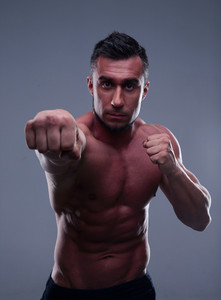 Fit man boxing over gray background