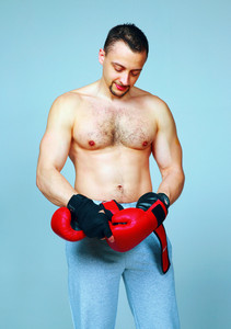 Fit man putting his boxing gloves, preparing for training over blue background