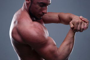 Fit man showing his muscles over gray background