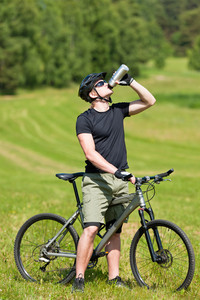 Fit young cycling man relax drink water in summer coutryside