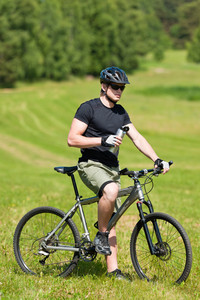 Fit young cycling man relax with water bottle in summer coutryside