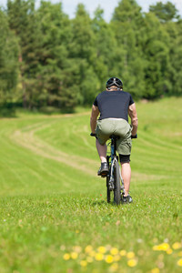 Fit young man cycling downhill mountain bike in summer coutryside