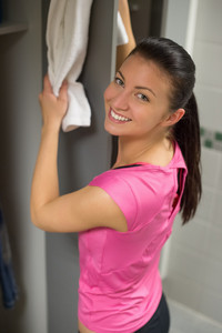 Fit young woman placing towel on open locker door at gym