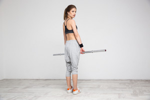 Fit young woman standing with barbell at the gym