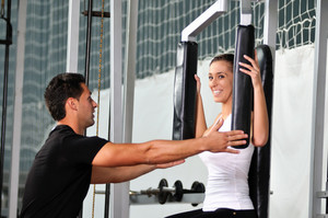 Woman in the fitness gym working out with personal trainer