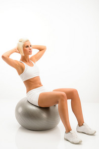 Fitness blond woman exercise on silver Pilates ball isolated white