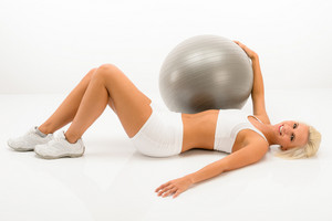 Fitness blonde woman exercising with gym ball lying white floor