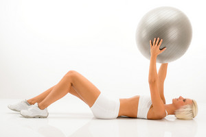 Fitness blonde woman exercising with Pilates ball lying white floor