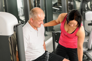 Fitness center active man exercising legs with personal trainer