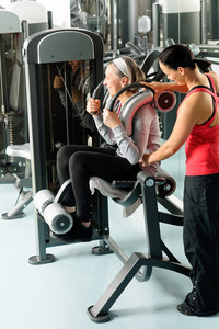 Fitness center senior woman exercise on machine with personal trainer
