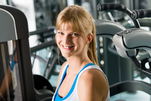 Fitness center smiling woman exercise on gym machine workout