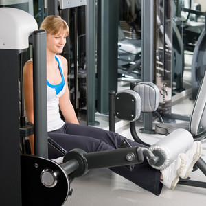 Fitness center young woman exercise legs on gym machine workout