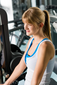 Fitness center young woman exercise on gym machine workout