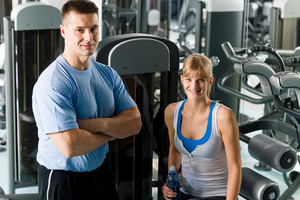 Fitness center young woman posing with personal trainer by gym machine