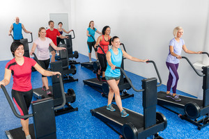 Fitness class walking on treadmill running deck at health club