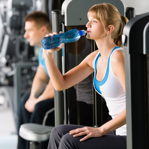 Fitness club young woman relax at weight machine drink water