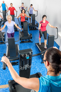 Fitness instructor leading treadmill running class at health club