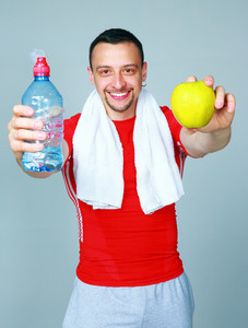 Fitness man just after a workout with water and apple on gray background