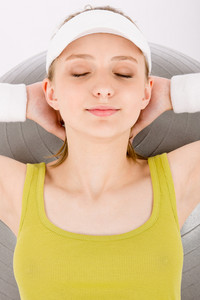 Fitness teenager woman with closed eyes in sportive outfit