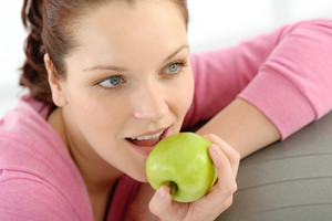 Fitness woman eat apple sportive outfit in gym