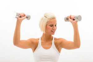 Fitness woman exercise biceps in studio lifting dumbbells