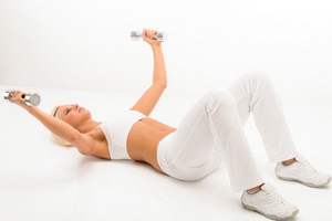 Fitness woman exercise in studio lifting dumbbells lying white floor