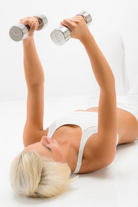 Fitness woman exercise in studio lifting weights lying white floor