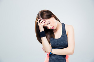 Fitness woman having headache over gray background