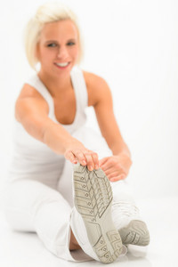 Fitness woman stretching her legs after gym sitting white floor