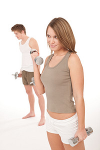 Fitness - Young healthy couple training lifting weights on white background